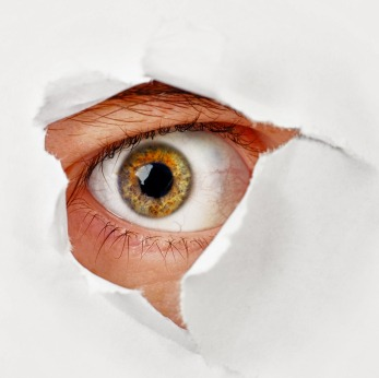 Eye looks through a hole in the paper - spy